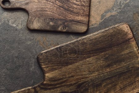 Photo pour Top view of brown wooden cutting boards on weathered grey background - image libre de droit