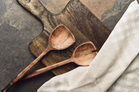 Photo for Top view of wooden cutting board with spatulas and napkin on weathered background - Royalty Free Image