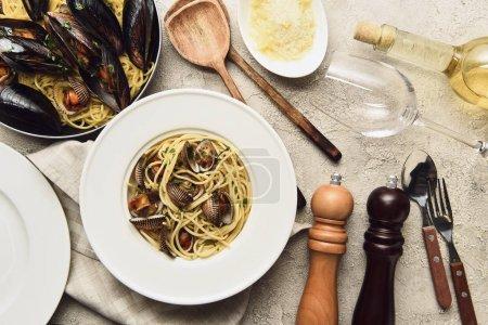 Blick von oben auf leckere Pasta mit Meeresfrüchten, serviert mit geriebenem Käse und Weißwein