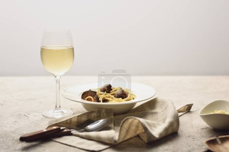 Photo for Italian pasta with seafood served with white wine, napkin and cutlery isolated on grey - Royalty Free Image