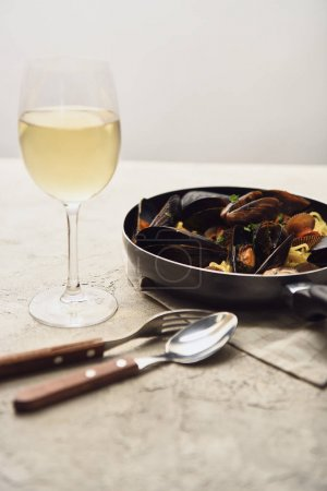 tasty Italian pasta with seafood served in frying pan with white wine, napkin and cutlery isolated on grey