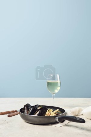 Photo for Delicious Italian pasta with seafood served in frying pan with white wine isolated on blue - Royalty Free Image