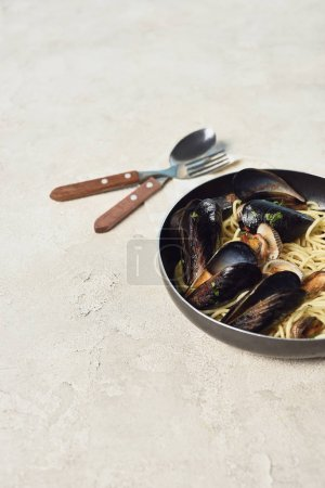 Photo for Tasty pasta with seafood in frying pan near cutlery on textured grey background - Royalty Free Image