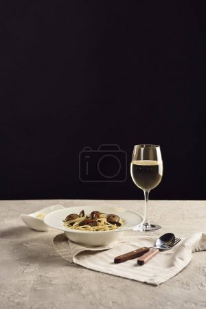 Photo for Delicious Italian spaghetti with seafood served with white wine and grated cheese on napkin near cutlery isolated on black - Royalty Free Image