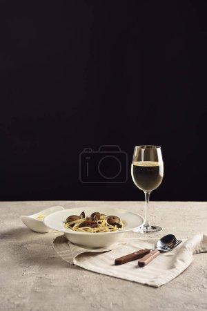 köstliche italienische Spaghetti mit Meeresfrüchten serviert mit Weißwein und geriebenem Käse auf Serviette in der Nähe von Besteck isoliert auf schwarz
