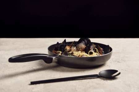Photo for Delicious Italian pasta with seafood served in frying pan near spatula isolated on black - Royalty Free Image