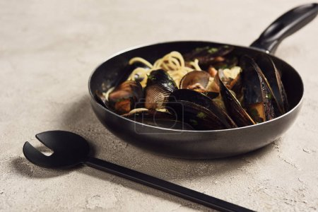 Photo for Delicious Italian pasta with seafood served in frying pan near spatula - Royalty Free Image