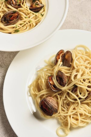 Photo for Close up view of delicious pasta with seafood served in two white plates - Royalty Free Image