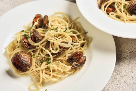 Photo for Close up view of tasty pasta with seafood served in two white plates - Royalty Free Image