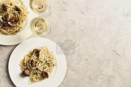 Photo pour Vue du dessus de délicieuses pâtes aux fruits de mer servies avec du vin blanc dans des verres sur une surface grise texturée avec espace de copie - image libre de droit