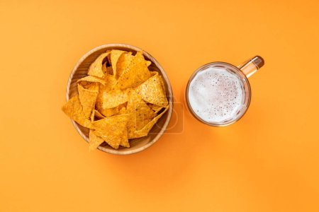 Photo for Top view of crispy nachos in wooden bowl near glass of beer on orange background, Mexican cuisine - Royalty Free Image