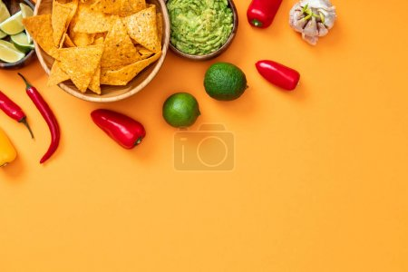 Photo for Top view of crispy nachos, guacamole and spices on orange background with copy space - Royalty Free Image