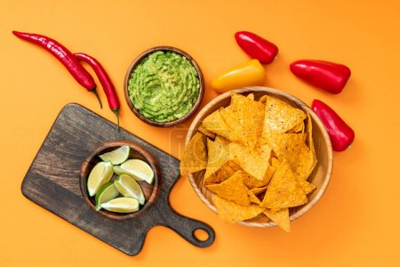 Photo for Top view of crispy Mexican nachos, guacamole, peppers, limes and wooden cutting board on orange background - Royalty Free Image