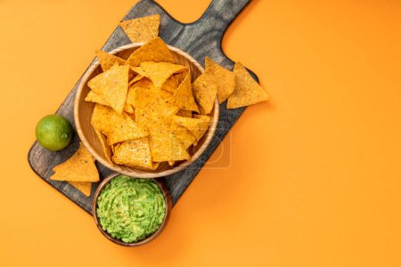 Foto de Top view of crispy Mexican nachos served with guacamole and lime on wooden cutting board on orange background - Imagen libre de derechos