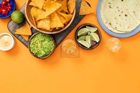 Photo for Mexican nachos served on wooden cutting board with guacamole, cheese sauce, peppers, limes, Tequila and tortillas on orange background with copy space - Royalty Free Image