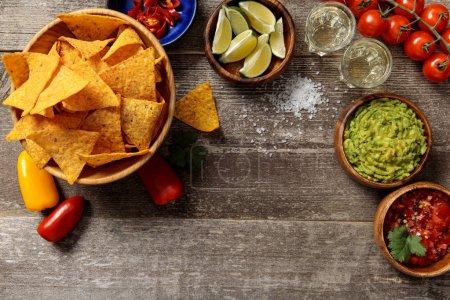 Photo pour Vue du haut des nachos mexicains servis avec tequila, guacamole et salsa sur table en bois altérée - image libre de droit