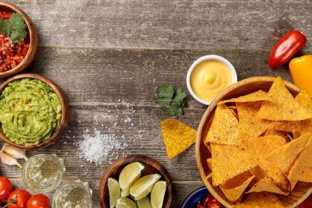 Photo pour Vue du haut des nachos mexicains servis avec sauce au fromage, guacamole et salsa sur table en bois altérée - image libre de droit