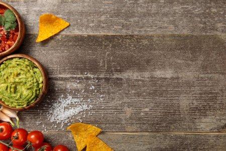 Photo pour Vue du haut des nachos mexicains servis avec guacamole et salsa sur table en bois altérée - image libre de droit
