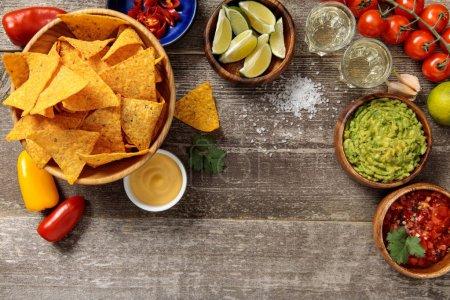 Photo pour Vue du haut des nachos mexicains servis avec guacamole, sauce au fromage et salsa sur table en bois altérée - image libre de droit