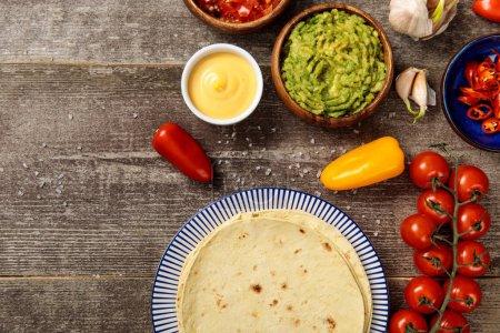 Photo pour Vue du haut de la tortilla mexicaine avec des épices, du guacamole, de la sauce au fromage et de la salsa sur une table en bois altérée - image libre de droit