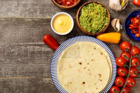 Photo for Top view of Mexican tortilla with guacamole, cheese sauce and salsa on weathered wooden table with copy space - Royalty Free Image