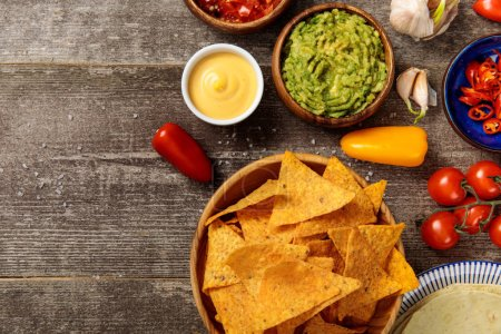 Photo for Top view of Mexican nachos served with guacamole, cheese sauce and salsa on wooden table - Royalty Free Image