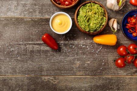Photo pour Vue du haut des nachos mexicains servis avec guacamole, sauce au fromage et salsa sur table en bois avec espace de copie - image libre de droit