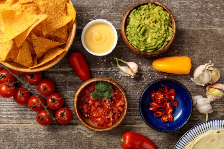 Photo for Top view of Mexican nachos served with guacamole, cheese sauce and salsa on wooden rustic table - Royalty Free Image