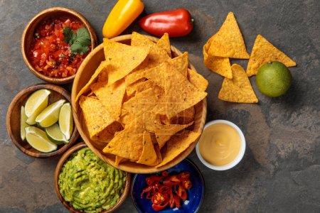 Photo pour Vue du haut des nachos mexicains servis avec guacamole, limes, sauce au fromage et salsa sur table en pierre - image libre de droit