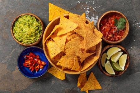 Photo pour Vue du haut des nachos mexicains servis avec guacamole, limes, piments et salsa sur table en pierre - image libre de droit