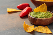 """Постер, картина, фотообои """"close up view of Mexican nachos with guacamole and chili peppers on stone table with copy space"""""""