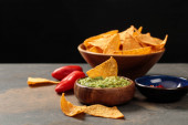 """Постер, картина, фотообои """"traditional Mexican nachos with guacamole and chili peppers on stone table isolated on black"""""""