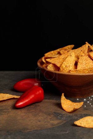 Photo for Crunchy Mexican nachos with salt and chili peppers on stone table isolated on black - Royalty Free Image