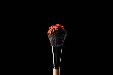Photo for Cosmetic brush with colorful orange powder isolated on black - Royalty Free Image