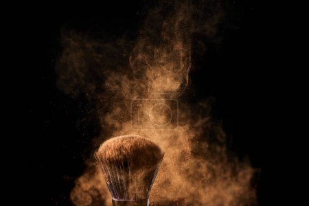 Photo pour Brosse cosmétique avec l'explosion colorée de poudre d'or sur le fond noir - image libre de droit