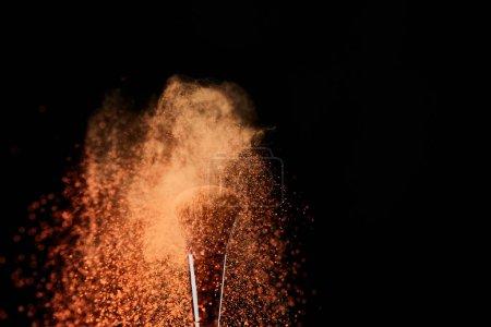 Photo pour Brosse cosmétique avec explosion orange de poudre sur le fond noir - image libre de droit