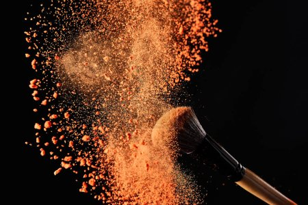 cosmetic brush with colorful orange powder explosion on black background