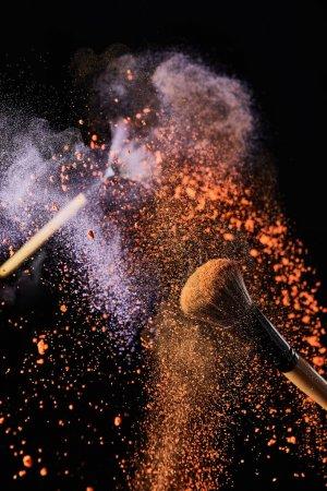 Photo pour Pinceaux cosmétiques avec explosion de poudre orange et violette colorée sur fond noir - image libre de droit