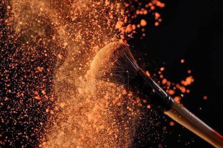 Foto de Cepillo cosmético con colorida explosión de polvo naranja - Imagen libre de derechos