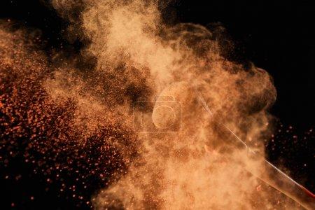 Photo pour Brosse cosmétique avec l'explosion colorée de poudre orange sur le fond noir - image libre de droit