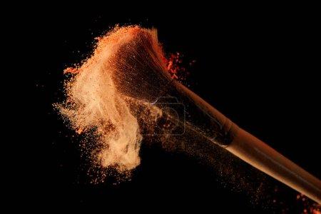 Foto de Cepillo cosmético con explosión de polvo naranja sobre fondo negro - Imagen libre de derechos
