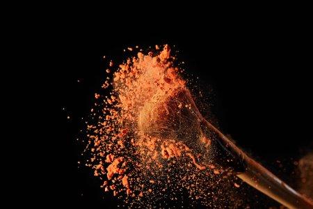 Foto de Cepillo cosmético con explosión de polvo de color naranja brillante sobre fondo negro - Imagen libre de derechos