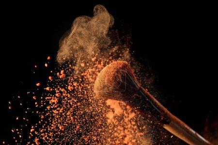 Photo pour Pinceau cosmétique avec explosion de poudre orange vif sur fond noir - image libre de droit