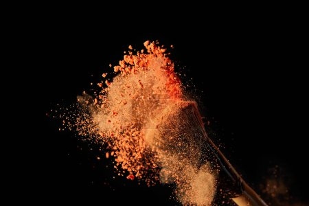 Photo for Cosmetic brush with colorful orange powder explosion on black background - Royalty Free Image