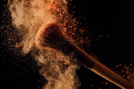 Foto de Cepillo cosmético suave con explosión de polvo naranja colorido en fondo negro - Imagen libre de derechos