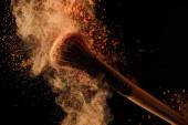 "Постер, картина, фотообои ""soft cosmetic brush with colorful orange powder explosion on black background"""