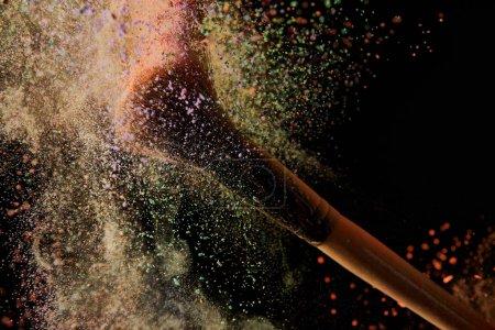 Foto de Cepillo cosmético con explosión de polvo colorido en fondo negro - Imagen libre de derechos