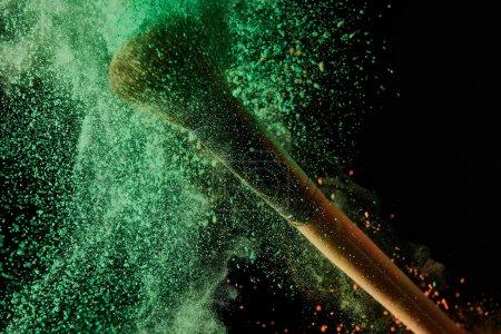 Photo pour Brosse cosmétique avec explosion de poudre verte sur le fond noir - image libre de droit