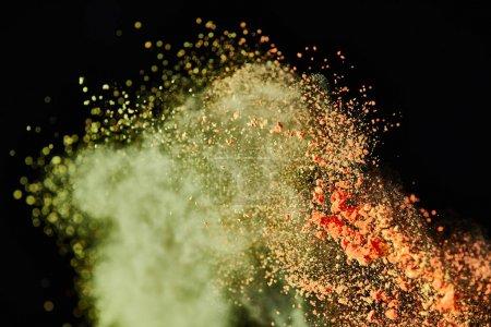 Foto de Cepillo cosmético con colorida explosión de polvo amarillo y naranja sobre fondo negro - Imagen libre de derechos