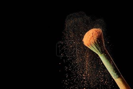Photo pour Brosse cosmétique avec la poudre orange colorée sur le fond noir - image libre de droit